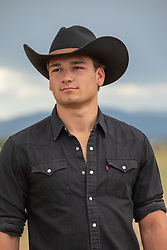 portrait of a good looking young cowboy outdoors