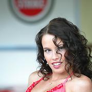 A BAR bikini clad girl poses on the car