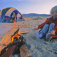 A youngster warms himself by a campfire in Eureka Valley, part of California's Death Valley National Park.