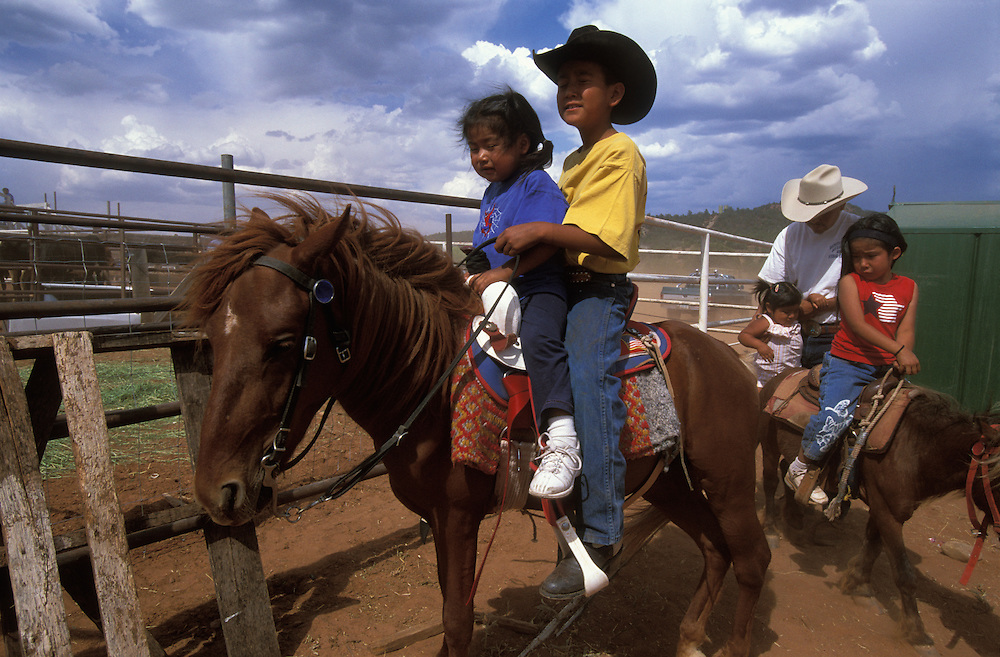 Two Apache children on horseback at a rodeo on The Fort Apache Indian Reservation, Arizona, USA. June 2004.