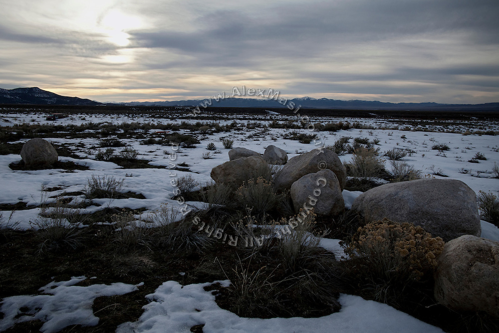 The sun is setting behind a clouded sky, over the hills surrounding the Goshute Reservation of Deep Creek Valley, on the Nevada-Utah border, USA.