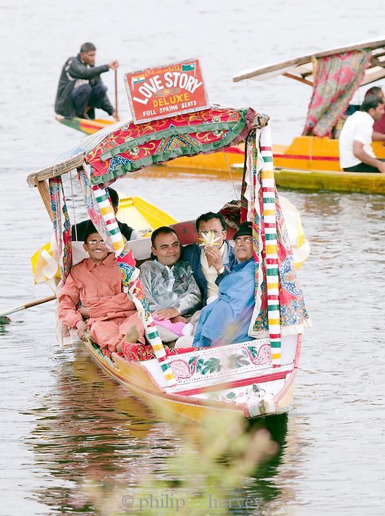 A group of local men in a shikara, a local wooden boat, on Lake Dal, Srinigar, Kashmir, India