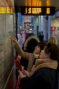 Young Chinese women travellers check the times and routes of buses at a bus stop on Bishopsgate, on 9th February 2017, in the City of London, England.