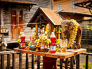 "11 FEBRUARY 2015 - BANGKOK, THAILAND: A Buddhist ""Spirit House"" in the Santa Cruz neighborhood. The neighborhood around the church is known for the Thai adaptation of Portuguese cakes baked in the neighborhood. Several hundred Siamese (Thai) Buddhists converted to Catholicism in the 1770s. Some of the families started baking the cakes. When the Siamese Empire in Ayutthaya was sacked by the Burmese, the Portuguese and Thai Catholics fled to Thonburi, in what is now Bangkok. The Portuguese established a Catholic church near the new Siamese capital. There are still a large number of Thai Catholics living in the neighborhood around the church.         PHOTO BY JACK KURTZ"