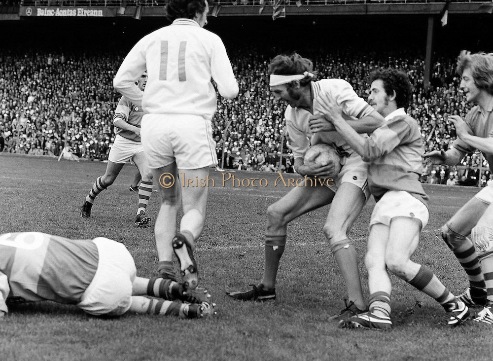 Armagh clings to the ball tight as Roscommon players tackle him from behind as another player is tackled to the ground during the All Ireland Senior Gaelic Football Semi Final Replay Roscommon v Armagh in Croke Park on the 28th August 1977. Armagh 0-15 Roscommon 0-14.