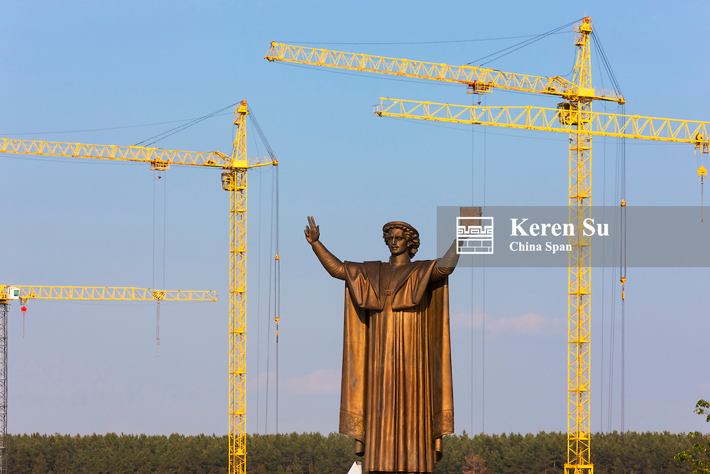 Statue of Francysk Skaryna with construction cranes, Minsk, Belarus