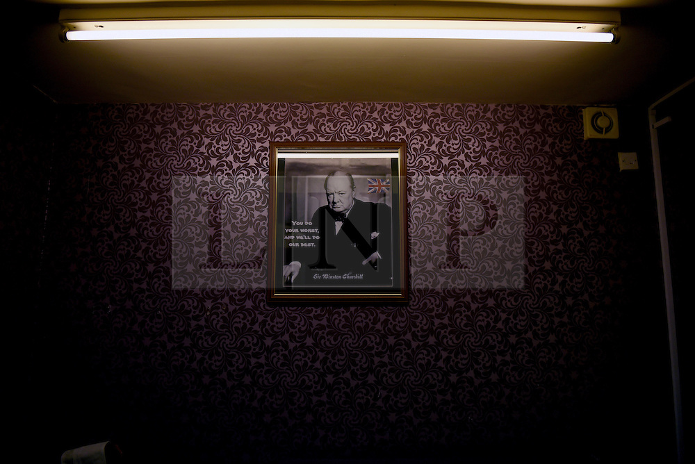 "© London News Pictures. ""Looking for Nigel"". A body of work by photographer Mary Turner, studying UKIP leader Nigel Farage and his followers throughout the 2015 election campaign. PICTURE SHOWS - A poster of Winston Churchill adorns the purple walls of the local UKIP candidate Bill Etheridge's office in Segdley, nr Dudley, West Midlands, on April 7th 2015. Nigel Farage is seen by many UKIP supporters as being a leader akin to his Churchill and they hark back to the spirit of his days of as Prime Minister. . Photo credit: Mary Turner/LNP **PLEASE CALL TO ARRANGE FEE** **More images available on request**"