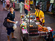 24 JULY 2018 - BANGKOK, THAILAND: A Thai woman buys fried chicken from a vender on Khao San Road in Bangkok. Khao San Road is Bangkok's original backpacker district and is still a popular hub for travelers, with an active night market and many street food stalls. The Bangkok municipal government plans to shut down the street market by early August because city officials say the venders, who set up on sidewalks and public streets, pose a threat to public safety and could impede emergency vehicles. It's the latest in a series of night markets and street markets the city has closed.    PHOTO BY JACK KURTZ
