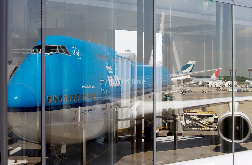 KLM Jumbo jet reflecting in window at the Narita international airport Tokyo Japan
