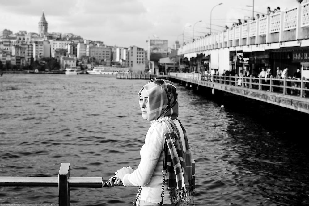 A young lady waits near Galata bridge in Istanbul