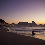 A couple dance and enjoy a tender moment as they witness the amazing sunrise at Rio de Janeiro's most famous beach Copacabana with Sugar Loaf mountain in the distance. Rio de Janeiro, Brazil. 21st July 2010. Photo Tim Clayton.
