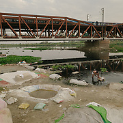 Men bleaching laundry then throwing it in the Yamuna. Laundry men cleaning using water from the Yamuna, nest to the old Iron Bridge.