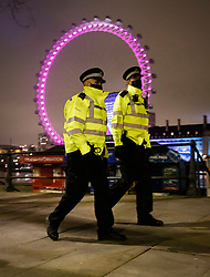 © Licensed to London News Pictures. 31/12/2020. London, UK. Police patrol the mostly quiet Embankment in sight of The London Eye ferris wheel ahead of midnight and a muted New Year's Eve in central London. Photo credit: Peter Macdiarmid/LNP