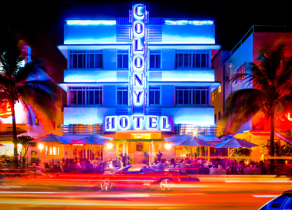 The iconic, neon-lit, Art Deco-style Colony Hotel and sidewalk cafe at night on Miami Beach's Ocean Drive with a red Ferrari parked in front. This South Beach landmark was designed in 1935 by architect Henry Hohauser.