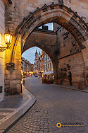 Arch of Lesser Town Bridge Tower on Charles Bridge with St Nicholas Church in Prague, Czech Republic