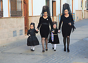 Two women and little girls dressed in black for Easter procession, Setenil de las Bodegas, Cadiz province, Spain