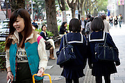 Street life in Tokyo - two girls in school uniform walking in the city centre. Tokyo has 13.01 million inhabitans, is the Japanese capital and the largest city in Japan. Tokyo, Japan, 23.10 2010.