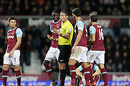 Referee Andre Marriner attempts to calm the situation with Cheikhou Kouyate of West Ham United, James Tomkins of West Ham United and Mark Noble, the West Ham United captain. Barclays Premier league match, West Ham Utd v Stoke city at the Boleyn Ground, Upton Park  in London on Saturday 12th December 2015.<br /> pic by John Patrick Fletcher, Andrew Orchard sports photography.