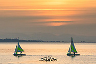 Two boats from the Crescent Beach Yacht Club sail past Blackie Spit during sunset.  Photographed from Blackie Spit at Crescent Beach in Surrey, British Columbia, Canada.