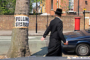 An Orthodox Jewish man walking down Portland Avenue past a Volvo and a sign for the local polling station taped to a tree.  The polling station for the local government elections of May 2006 was in Stamford Hill library.