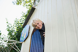 Little boy looking out of tree house