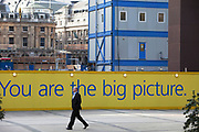 Sign reads 'You are the big picture' on a hoarding blocking a construction sitte in he City of London. A man in a business suit walks past.