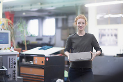 Young worker carrying box while standing at printing press