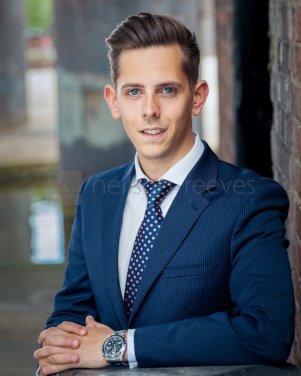 Corporate portrait taken outdoors in Castlefield area of Manchester with canal in background and businessman in blue suit resting hands on barrier