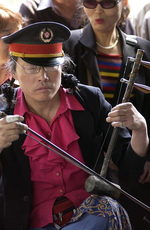 Beijing musician plays traditional instrument.