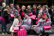 Group of girls with their hair in curlers and wearing pink. A dance group from Liverpool visiting London for a competition, go out shopping at Victoria's Secrets on New Bond Street.