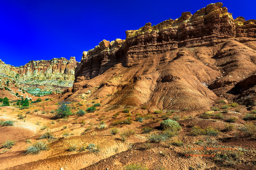 Arid  Beauty: As arid this scene is it is equally beautiful, so dramatically coloured with striated cliffs, rock sprees and flood rivulets in Capital Reef National Park, Utah, United States of America.