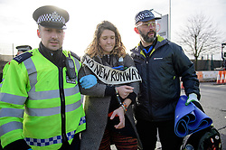 "© Licensed to London News Pictures. 19/11/2016. Heathrow, UK. An activist reported to be SOPHIE LYSACZANKO , wearing the slogan ""NO NEW RUNWAY"" while being arrested near Heathrow Airport. A group of activists stage attach themselves to a road surrounding  Heathrow Airport, during a demonstration against the expansion of Heathrow Airport and the building of a third runway. Some activists  threatened ""direct action"". Photo credit: Ben Cawthra/LNP"