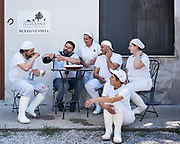 Alberto and his employees posing for a portrait and enjoying a wine and cheese break after making mozzarella and ricotta.
