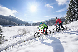 Mountain bikers riding bicycle in snow