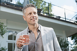 Man handsome relaxed standing drinking fruit juice