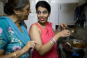 An Indian housewife at home with her mother-in law in New Delhi, cooks her favourite dish in her kitchen, New Delhi, India