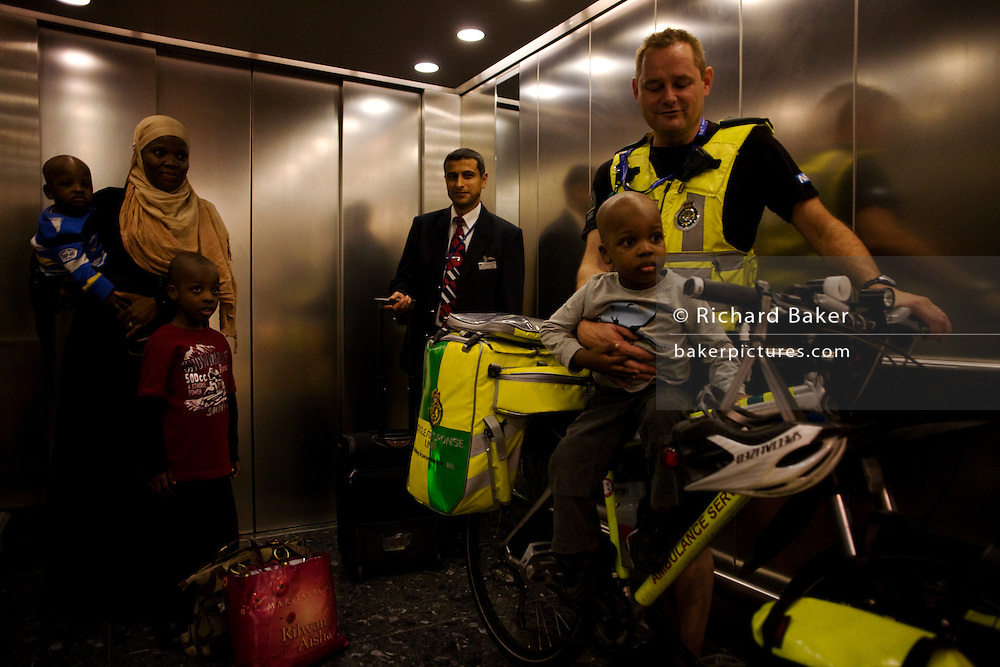 NHS Paramedic cyclist Responders holds a young passenger in a lift (elevator) within Heathrow Airport's terminal 5