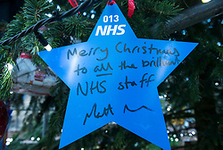"© Licensed to London News Pictures; 17/11/2020; Bristol, UK. A star signed by the Health Secretary MATT HANCOCK is placed on a giant Christmas tree for the ""Florence NHS Christmas Tree"" Thank You NHS Stars Fundraiser, with blue stars signed by among others the UK Prime Minister Boris Johnson, Health Secretary Matt Hancock and Deputy Chief Medical Officer Jonathan Van-Tam. For the 10th year Clifton Village in Bristol has a 50ft illuminated Christmas tree, the tallest in any UK village. Photo credit: Simon Chapman/LNP."
