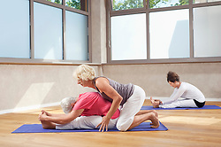 Male trainer teaching group Yoga exercises