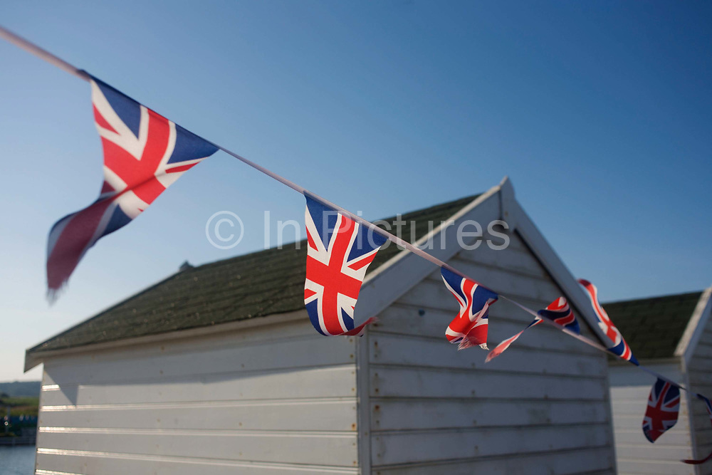 Union Jack flags flutter on a summer breeze at the Suffolk seaside town of Southwold, Suffolk, known for its lack of branded commercialism. The triangular pennants flutter in the wind in a quintessential scene of Englishness. Southwold is a small town on the North Sea coast, in the Waveney district of the English county of Suffolk. It is located on the North Sea coast at the mouth of the River Blyth within the Suffolk Coast and Heaths Area of Outstanding Natural Beauty. The town is around 11 miles (18 km) south of Lowestoft and 29 miles (47 km) north-east of Ipswich.