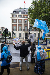 London, UK. 5th August, 2021. Activists from Uyghur Solidarity Campaign UK and other supporting groups hold placards and wave Uyghur flags opposite the Chinese embassy in support of the Uyghur people's struggle for freedom. Activists highlighted the Chinese government's persecution and forced assimilation of Uyghurs, Kazakhs and other indigenous people in East Turkestan and Xinjiang and called for them to have the right to determine their own futures through a democratic process.