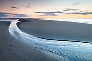 At dusk, a small channel drains into the North Sea at low tide, Brancaster beach. North Norfolk coast, East Anglia.