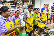 11 SEPTEMBER 2013 - BANGKOK, THAILAND:  Workers in a food shop throw pieces of dough into vats of boiling water to make dumplings in the Chinatown section of Bangkok. Thailand in general, and Bangkok in particular, has a vibrant tradition of street food and eating on the run. In recent years, Bangkok's street food has become something of an international landmark and is being written about in glossy travel magazines and in the pages of the New York Times.        PHOTO BY JACK KURTZ