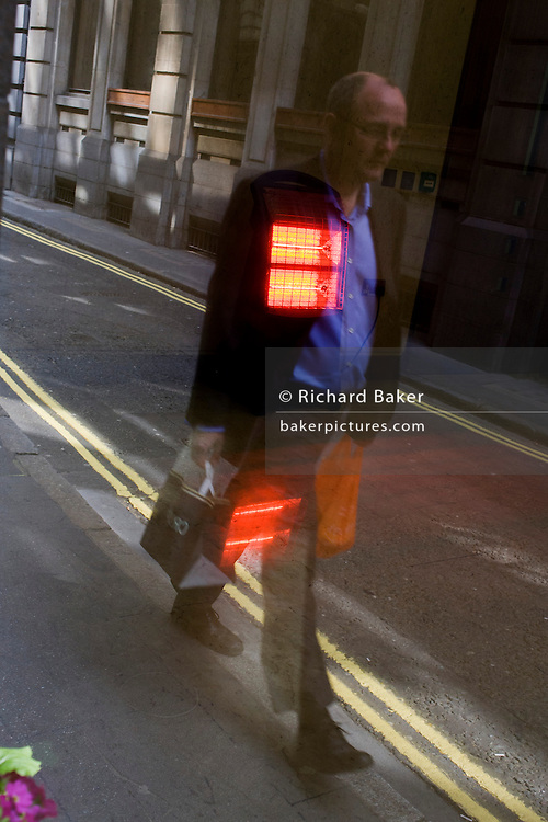 Man walks along narrow City of London lane, with reflection of office heater over his chest.