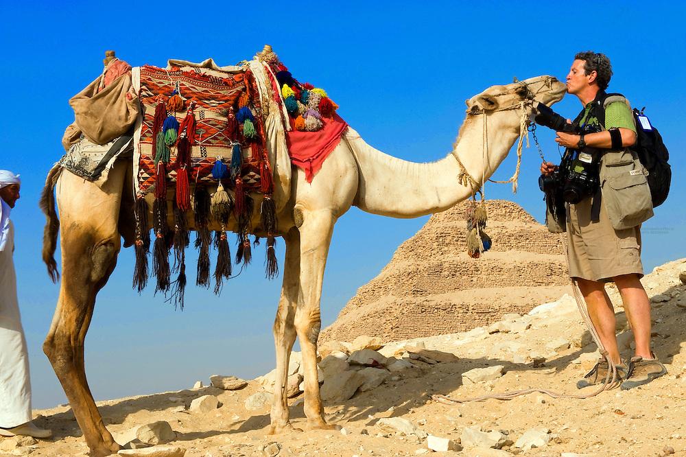 Photographer Blaine Harrington bonds with the camels at Step Pyramid of King Zoser, Saqqara, Egypt