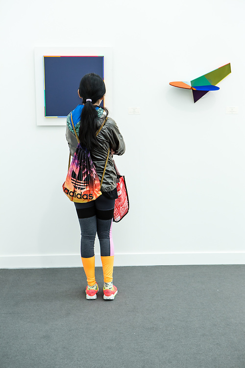 """New York, NY - 5 May 2017. The opening day of the Frieze Art Fair, showcasing modern and contemporary art presented by galleries from around the world, on Randall's Island in New York City. A young woman in colorful clothing looks at two works by Marc Vaux in the Bernard Jacobson gallery, the painting """"King's Blue"""" on the left, and an untitled mixed media piece."""