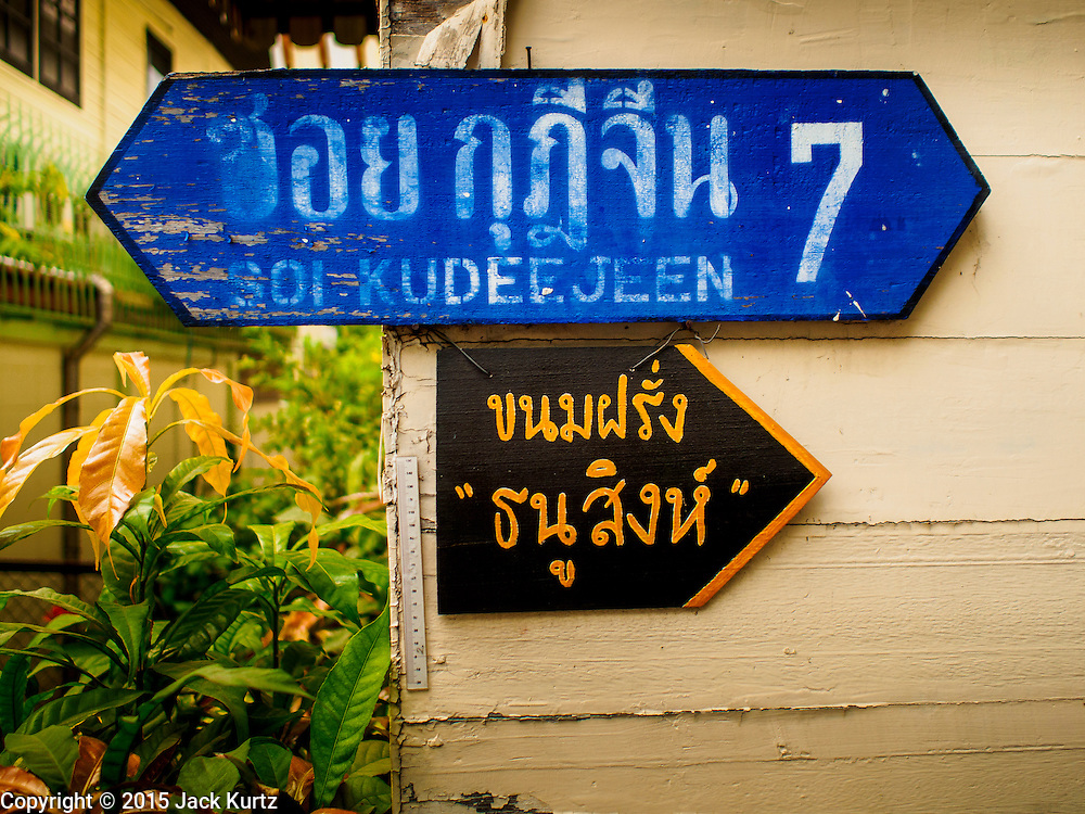 11 FEBRUARY 2015 - BANGKOK, THAILAND: A detail photo of street signs near Santa Cruz Church in the Thonburi section of Bangkok. The bottom, yellow and black sign, is pointing the way to Thanusingha Bakery, the top, blue, sign is the name of the street. The neighborhood around the church is known for the Thai adaptation of Portuguese cakes baked in the neighborhood. Several hundred Siamese (Thai) Buddhists converted to Catholicism in the 1770s. Some of the families started baking the cakes. When the Siamese Empire in Ayutthaya was sacked by the Burmese, the Portuguese and Thai Catholics fled to Thonburi, in what is now Bangkok. The Portuguese established a Catholic church near the new Siamese capital. There are still a large number of Thai Catholics living in the neighborhood around the church.         PHOTO BY JACK KURTZ