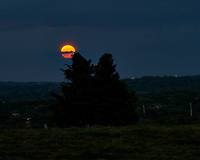 Strawberry Full Moon Rising Through the Clouds over Montgomery Township. Image taken with a Nikon D5 camera and 70-200 mm f/2.8 VR lens (ISO 100, 200 mm, f/11, 6 sec). Raw image processed with Capture One Pro.