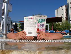 British tourist reading her book by hotel swimming pool; Marmaris; Turkey