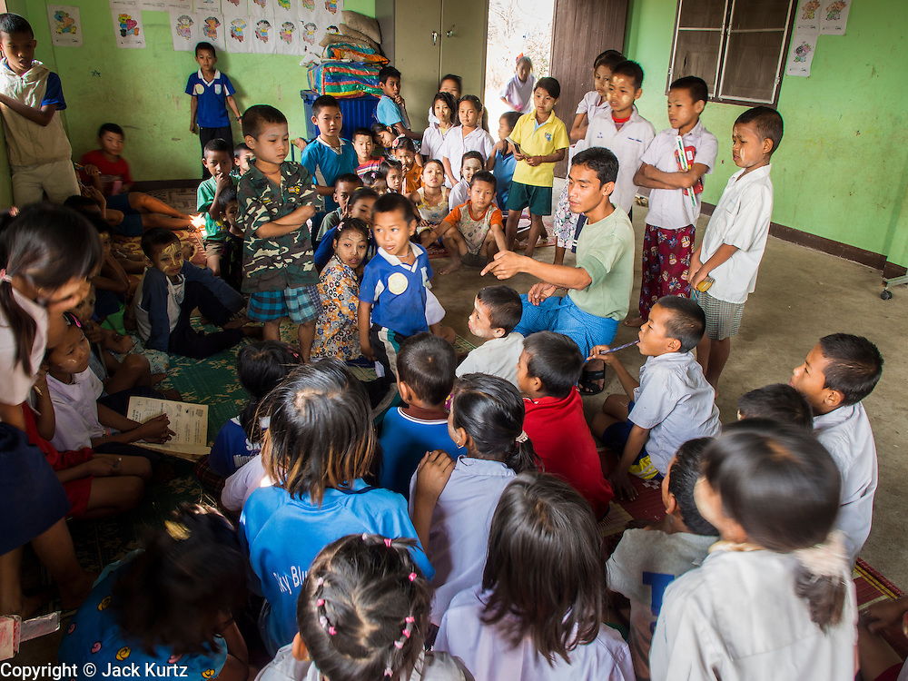 04 MARCH 2014 - MAE SOT, TAK, THAILAND: A teacher in a classroom at the Sky Blue School in Mae Sot. There are approximately 140 students in the Sky Blue School, north of Mae Sot. The school is next to the main landfill for Mae Sot and serves the children of the people who work in the landfill. The school relies on grants and donations from Non Governmental Organizations (NGOs). Reforms in Myanmar have alllowed NGOs to operate in Myanmar, as a result many NGOs are shifting resources to operations in Myanmar, leaving Burmese migrants and refugees in Thailand vulnerable. The Sky Blue School was not able to pay its teachers for three months during the current school year because money promised by a NGO wasn't delivered when the NGO started to support schools in Burma. The school got an emergency grant from the Burma Migrant Teachers' Association and has since been able to pay the teachers.    PHOTO BY JACK KURTZ